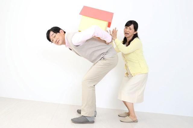 家を担ぐ男性と女性