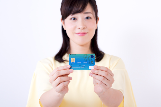 クレジットカードを持つミドル女性