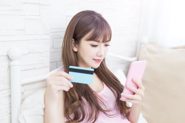 携帯とdカードを持つ女性
